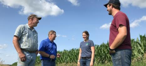 Landowner Mark Riestenberg and East Otter Tail SWCD staff talk at the edge of an irrigated corn field