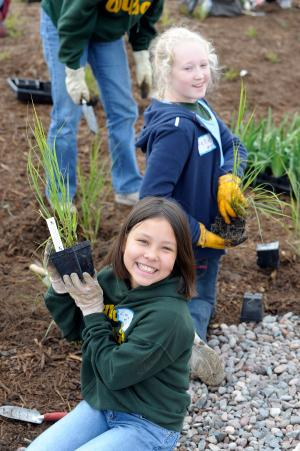 Kids planting grasses and wildflowers during a planting event